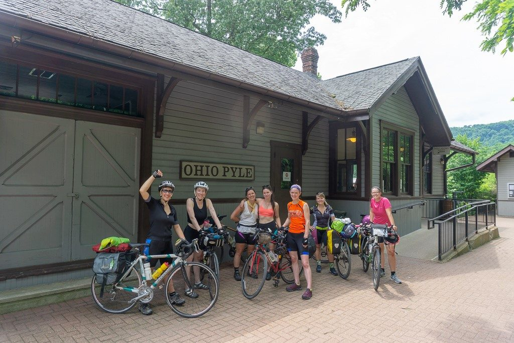 Seven women standing with their bikes in front of the Ohiopyle station.